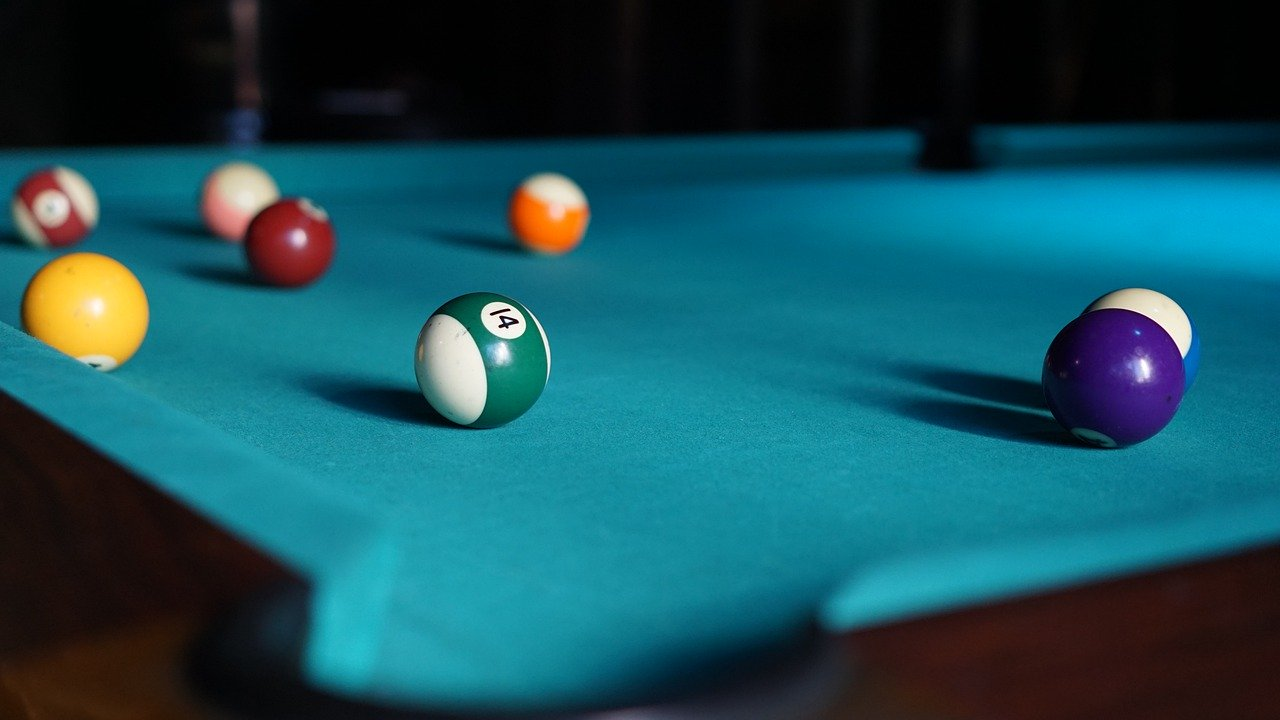 Learn how to clean a pool table for maximum playability represented by a poll table and 6 billird balls