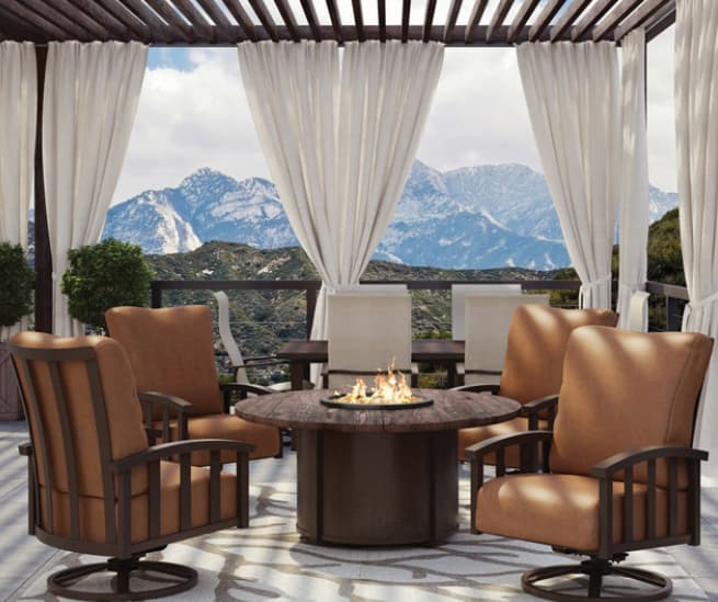 Enclosed gazebo with drapes with deep seating around outdoor gas fire table