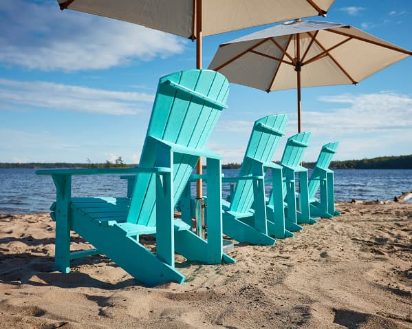 Turquoise adirondack chairs lined up facing the water