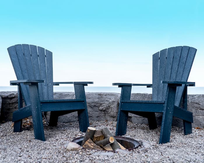 Two blue Muskoka chairs by the fire pit